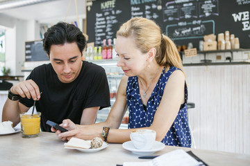 Friends using smart phone at table in coffee shop