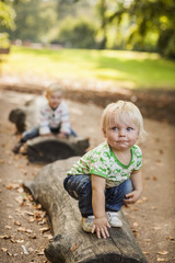 Baby boy crouching on log at park
