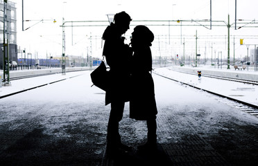 Silhouette of couple standing face to face outdoors