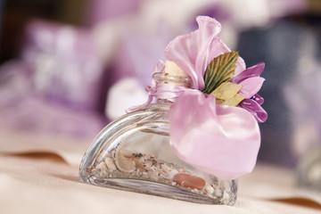 Bomboniera di vetro con sabbia e conchiglie e  con fiocchi rosa esterni