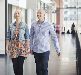 Happy young friends walking on corridor of shopping mall
