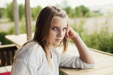 Portrait of serious girl leaning on retaining wall