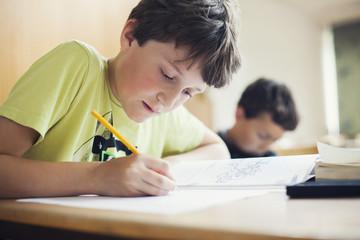 Boy writing in book on desk at school