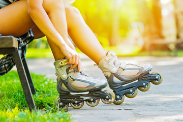 Young woman in park putting on roller blades on sunny summer day