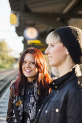 Portrait of beautiful woman with happy friend at railroad station