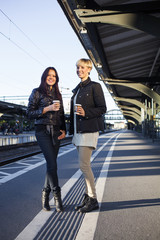 Portrait of young female friends with coffee on railroad station