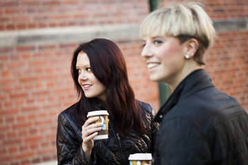 Happy woman with coffee cups against brick wall