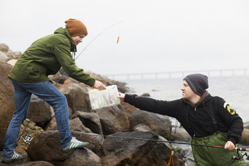 Teenage boy giving fishing tackle box to man on rocky shore