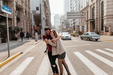 Beautiful couple hugging on crosswalk