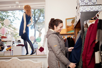 Happy woman choosing dress at clothing store