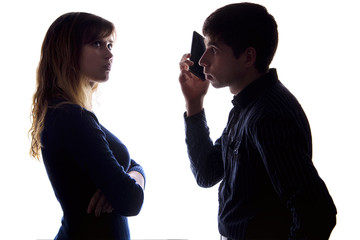 Silhouette of a young woman is jealous and offended because of the fact that a man communicates by phone