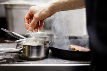 Cropped hand of chef cooking at commercial kitchen