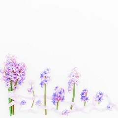 Bouquet of hyacinth flowers and shabby tapes on white background. Flat lay, top view.