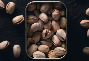 Roasted pistachios in metal jar on the black background. Dark food photography. Top view.