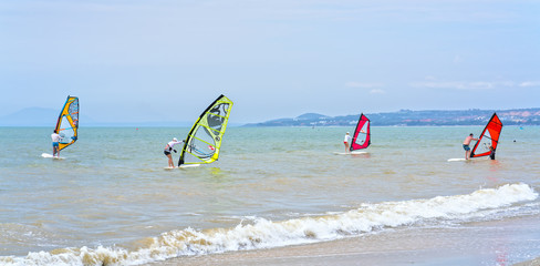 Mui Ne, Vietnam - February 19th, 2017: Guests are practice games windsurfing sail on the bay on a beautiful summer afternoon in Mui Ne, Vietnam