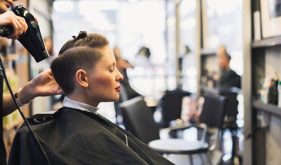 Stylish fashionable young girl in a hairdresser. The portrait of a girl who makes a hipster's hair, with shaven temples.