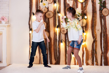 A little boy and girl are playing led lamps. They hold the bulbs in their hands.