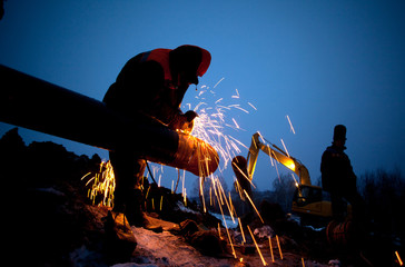 A worker grinds a pipe on the construction of a pipeline