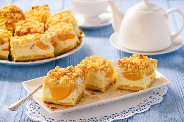 Cheesecake with peaches on blue wooden background.