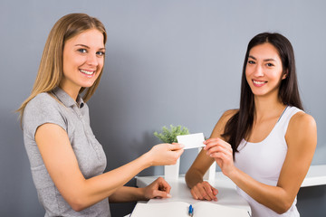 Woman receptionist of the fitness center is giving a membership card to sporty woman who came to exercise.