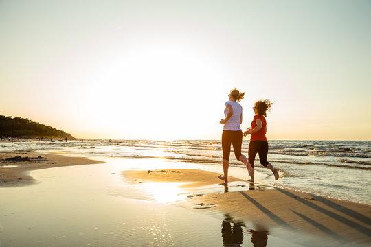 Two women running on beach