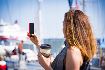 Beautiful woman taking  photo with smart phone. Picture of harbor with sailboats, seaside. Sunny summer bay. Taking selfie and drinking coffee. Vacation destination. Helsinki, Finland