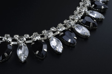 black and white jewelry with dark background. low key picture style of commercial product.