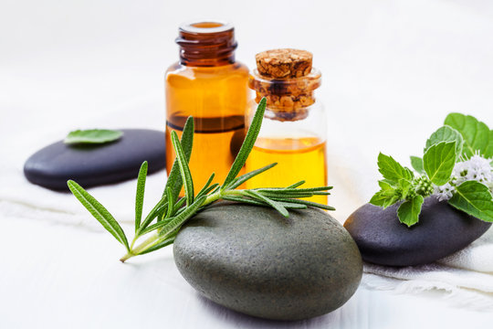 Alternative health care and herbal medicine . Close Up fresh rosemary and peppermint leaves on spa stone with essential oil bottle setup on white wooden table. Selective focus shallow depth of field.