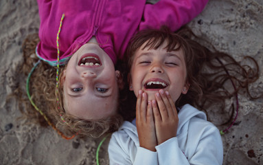 young friends laughing while lying on the beach