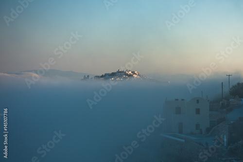Top of Caldera cliff above the fog at sunny sunrise, village