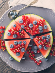 Slice of watermelon served as cake or pizza with fresh berries on rustic background