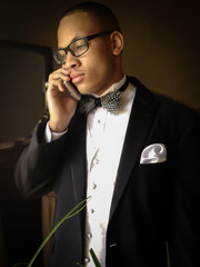 Young Handsome black man in a tuxedo on a cellphone in front of window with a soft look to it