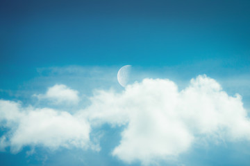 Half moon on blue sky have white cloud.