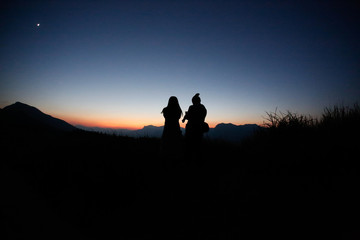 young couple  silhouette  hill