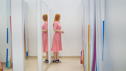 Young woman with glasses trying pink dress near mirror in fitting room - shopping concept