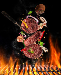 Flying raw milled beef meat with ingredients above grill fire
