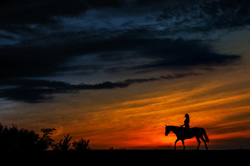 A silhouette of a woman riding a horse at sunset