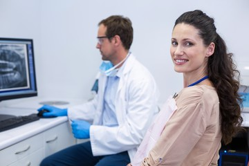 Female patient smiling while dentist working