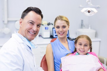 Portrait of dentist with young patient and his mother