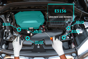 Augmented reality , customer service concept. Engineer using AR glasses instruction manual application to fix maintenance car engine.
