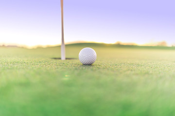 Golf ball close to hole on green, close up super wide angle.  Lots of opportunity for copy text.