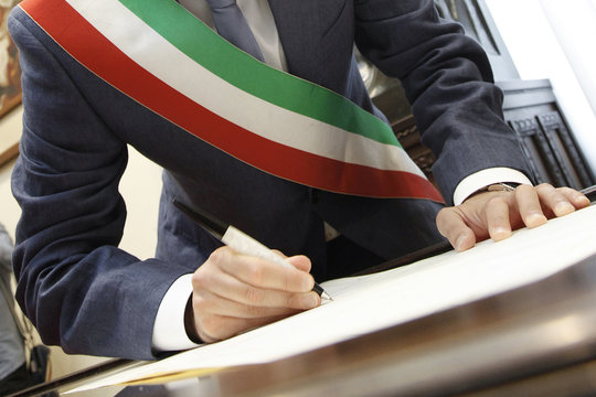 foto b/n della mano di un sindaco con fascia tricolore che firma con una penna un documento