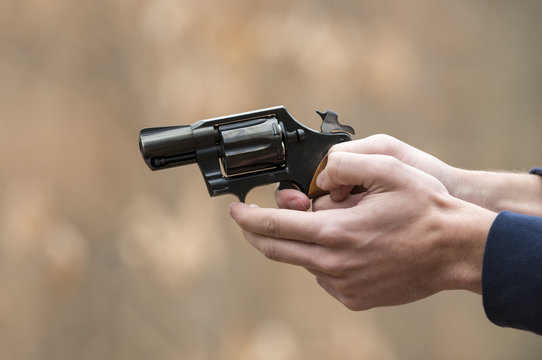 Hands holding a pointing a hand gun pistol with a shallow depth of field