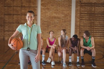 Female coach standing with basketball in basketball court