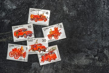 Moscow, Russia - April 20, 2017: Set of randomly lying postage stamps printed in Cuba shows fire engines, series, circa 1977. Copy space for your text on a dark black cement background.