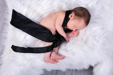 Newborn baby boy sleeping with a black tie