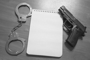Handgun handcuffs and notepad on the table with copy space black and white photography