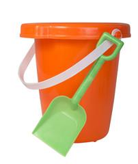 Bright orange plastic bucket with green shovel isolated on white