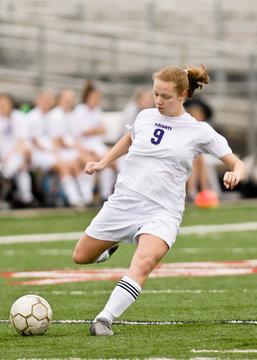 Female soccer player shooting on goal