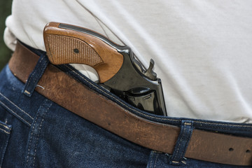 Pistol for personal protection stored in waist of pants